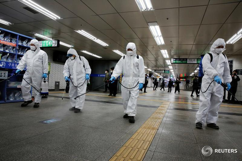 Employees from a disinfection service company sanitize a subway station amid coronavirus fears in Seoul
